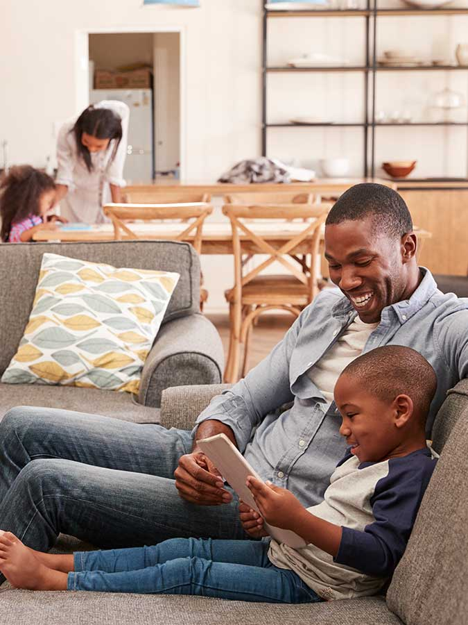 Father and son watching a tablet on the couch, mother and daughter at the table in the background